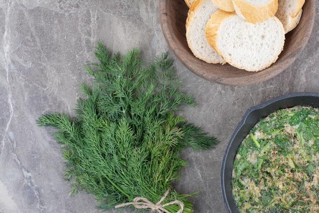 Een donkere pan gebakken eieren met groenen en wit brood op marmeren achtergrond. hoge kwaliteit foto