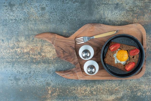 Een donkere pan met gebakken ei en sneetjes bruin brood op een houten bord
