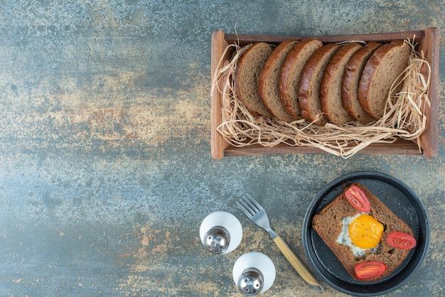 Een donkere pan met gebakken ei en sneetjes bruin brood op marmeren achtergrond