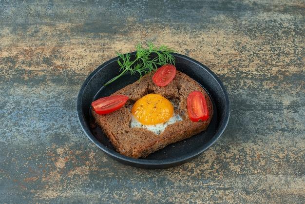 Een donkere pan met gebakken ei en tomaat op marmeren achtergrond