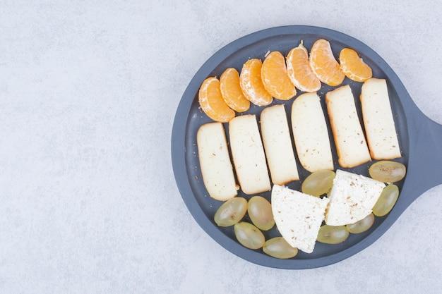 Een donkere pan met gesneden brood en fruit. hoge kwaliteit foto Gratis Foto