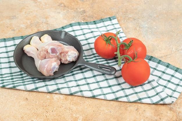 Een donkere pan met ongekookte kippenpoten en tomaten