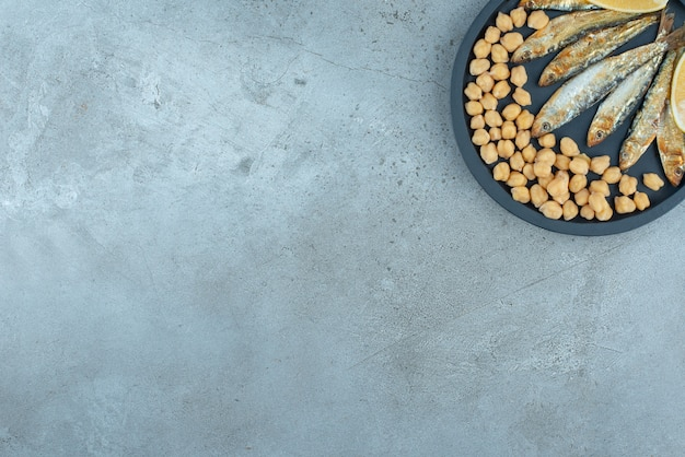 Een donkere pan met vis en erwten op een grijze achtergrond. hoge kwaliteit foto Gratis Foto