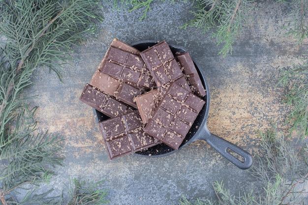 Een donkere pan vol gesneden chocolaatjes op marmeren achtergrond. hoge kwaliteit foto