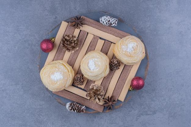 Een donkere plaat met koekjes en dennenappels van kerstmis