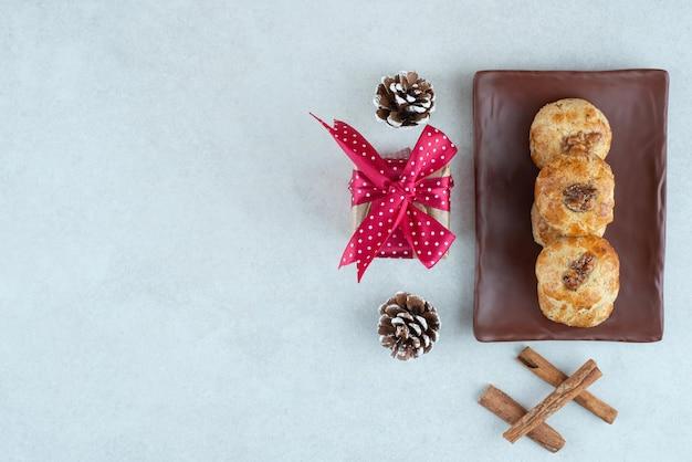 Een donkere plaat van koekjes met een klein kerstcadeautje en dennenappels.