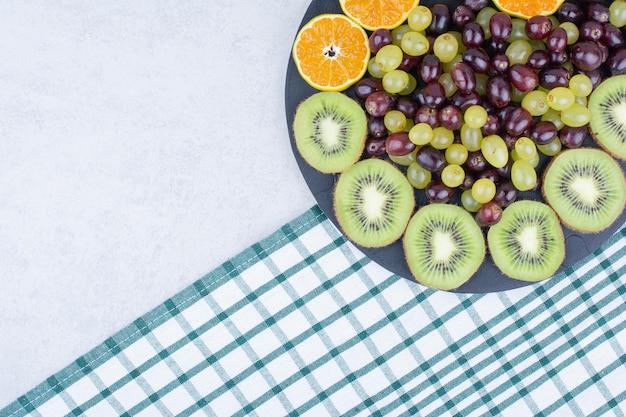 Een donkere plaat vol druiven, kiwi en sinaasappel op tafellaken.