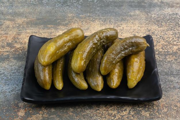 Een donkere plaat vol heerlijke ingemaakte komkommers op witte achtergrond. hoge kwaliteit foto