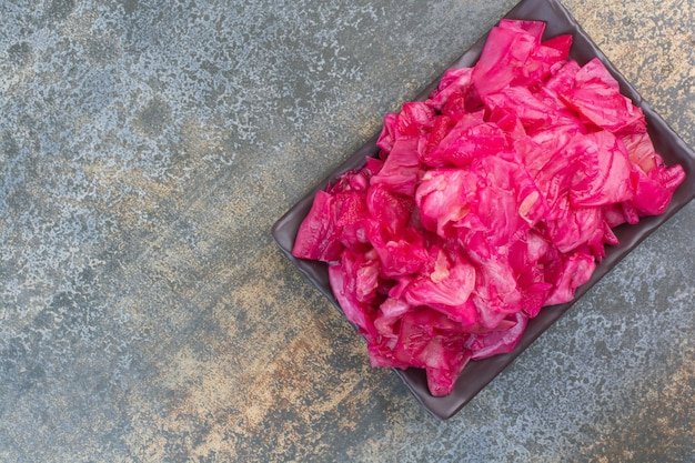 Een donkere plaat vol rode zoute kool op marmeren achtergrond. hoge kwaliteit foto