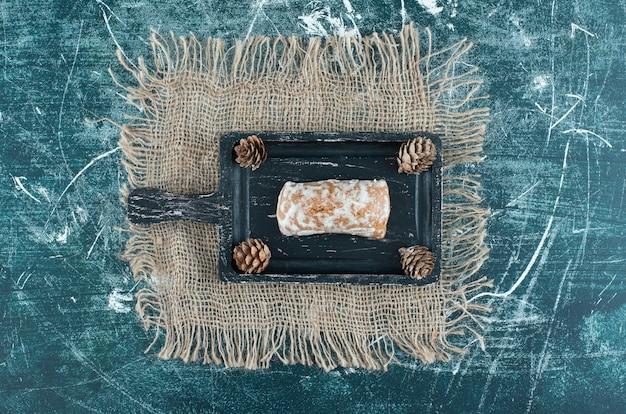 Een donkere plank met lekkere peperkoek en dennenappels. hoge kwaliteit foto