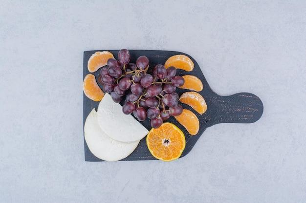 Een donkere snijplank met gesneden kaas en fruit.