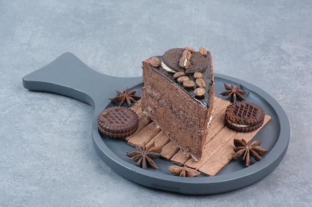 Een donkere snijplank van zoete cake en steranijs