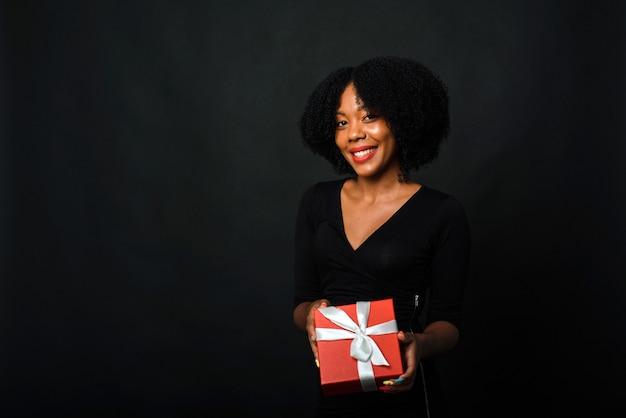 Een donkere vrouw met een afrokapsel geeft een cadeau
