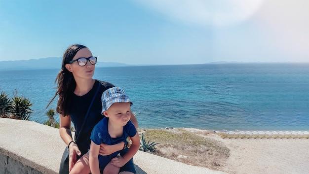Een donkerharige blanke vrouw met een baby in haar armen op vakantie zit tegen de achtergrond van