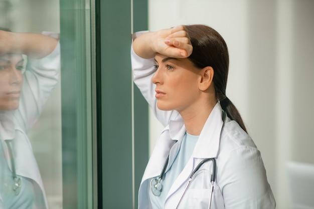 Een donkerharige dokter die bij het raam staat en nadenkend kijkt