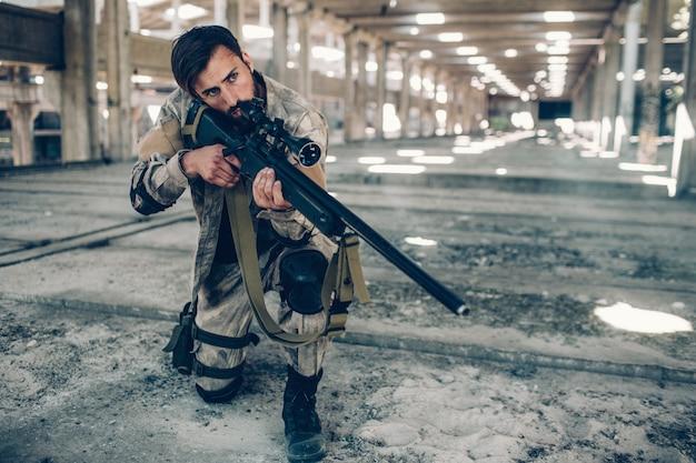 Een donkerharige man staat alleen in een lange hangar. hij heeft een knie op de grond gelegd en het geweer in handen gehouden. de mens kijkt naar rechts. hij is heel voorzichtig maar klaar om te schieten.