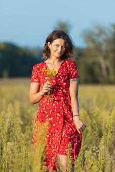 Een donkerharige vrouw glimlacht, loopt langs het groene veld gekleed in een rode jurk