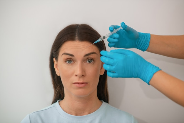 Een donkerharige vrouw van middelbare leeftijd die een mooie injectieprocedure ondergaat