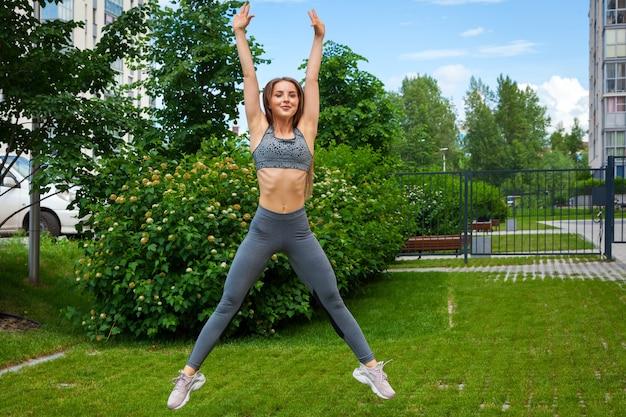 Een donkerharige vrouwencoach in een sportieve korte top en gymlegging doet sportoefeningen en springt op een zomerdag in een park op een groen gazon