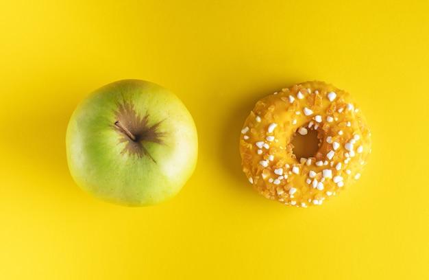 Een donut en een appel op roze en geel achtergronddieetconcept