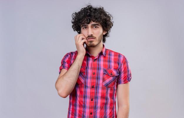 Een doordachte knappe man met krullend haar in een geruit overhemd die de hand op het gezicht houdt