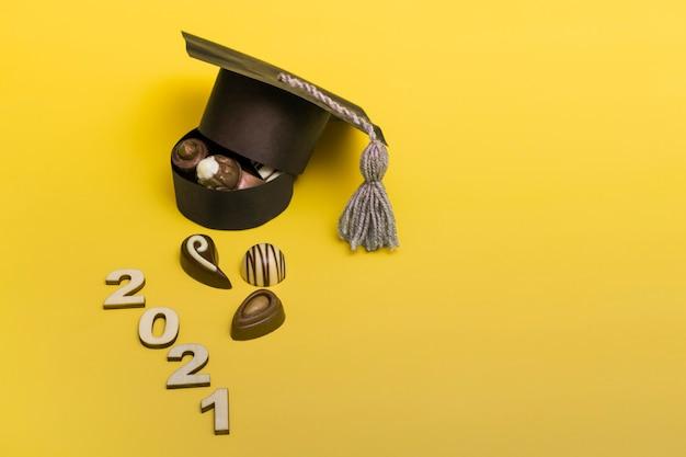 Een doos bonbons in de vorm van een afstudeerhoed. chocolade dag concept. afstuderen 2021 op gekleurde achtergrond.