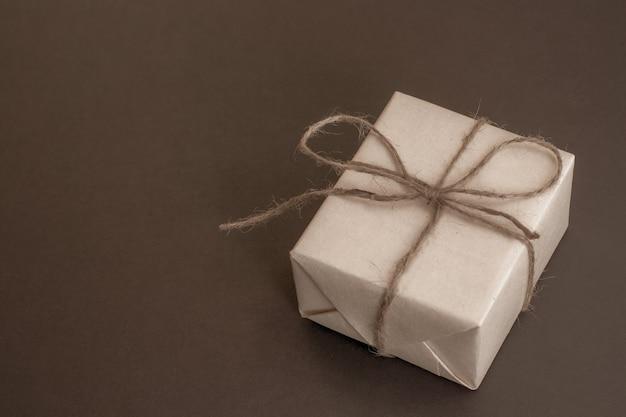 Een doos grijs kraftpapier vastgebonden met een henneptouw op donkergrijs