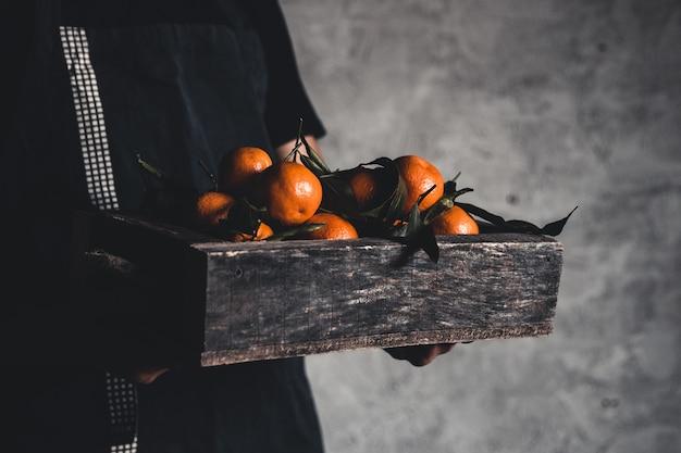 Een doos mandarijn in mannelijke handen op een grijze achtergrond. boer, eco fruit, eten. pnov2019