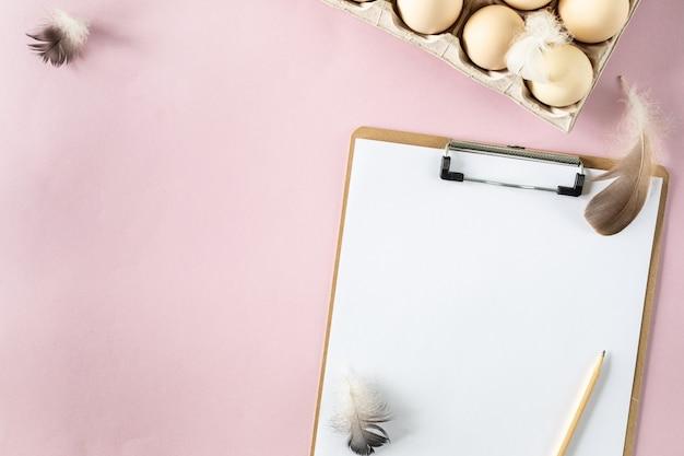 Een doos met biologische verse kippeneieren en een slipboard op een roze tafel. milieuvriendelijke eierproductie. landbouw. ingrediënten bakken. uitzicht van boven. kopieer ruimte. horizontaal. verticaal.