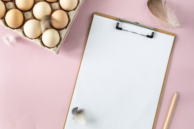 Een doos met biologische verse kippeneieren en een slipboard op een roze tafel. milieuvriendelijke eierproductie. landbouw. ingrediënten bakken. uitzicht van boven. kopieer ruimte. horizontaal.