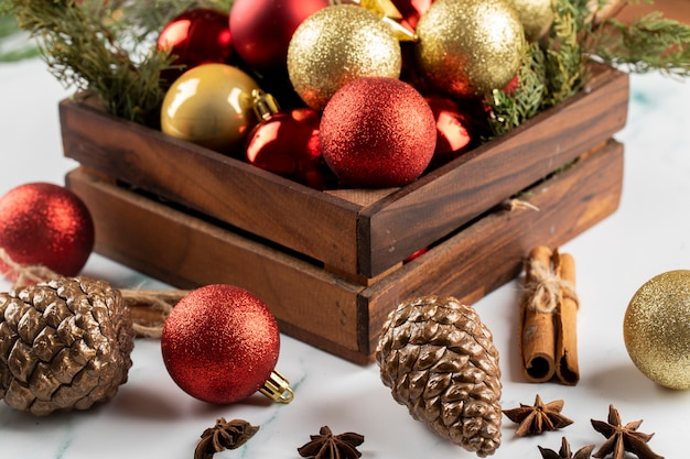 Een doos met rode en gouden kerstboomversieringen op de tafel.