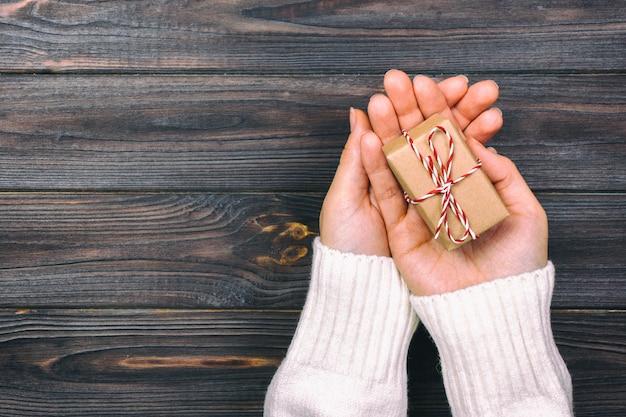 Een doos van de holdingskerstmis van de vrouwenhand op hand op donkere houten