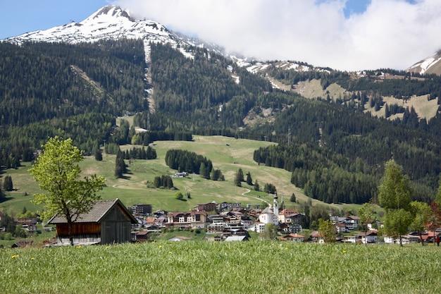 Een dorp met veel gebouwen in een bergachtig landschap omgeven door groene bomen