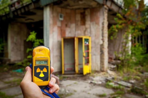 Een dosismeter in handen met een radioactiviteitsniveau in de stad pripyat, een spookstad van de kerncentrale van tsjernobyl die in 1986 werd getroffen door een nucleaire ramp, de uitsluitingszone van tsjernobyl, oekraïne.