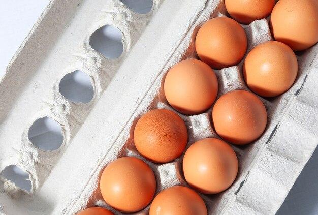 Een dozijn bruine eieren in karton