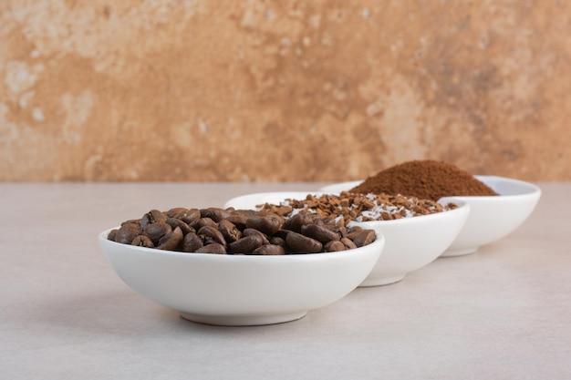 Een drie witte plaat vol koffiebonen en cacaopoeder