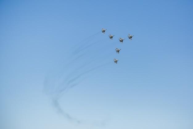 Een driehoekige formatie van een groep van zes russische militaire straaljagers die hoog in de blauwe lucht vliegen