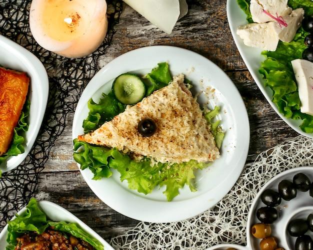 Een driehoekige mimosa salade gegarneerd met sla en komkommer