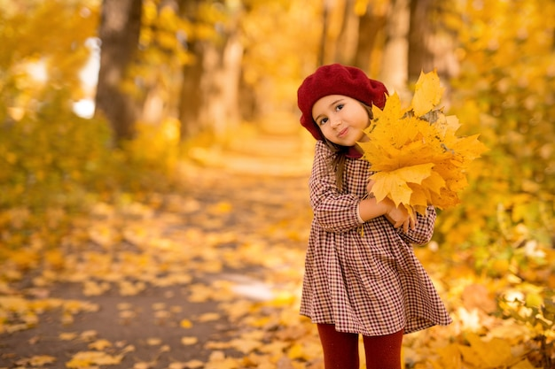Een driejarig meisje met een boeket esdoornbladeren in haar handen in het park op een herfstdag