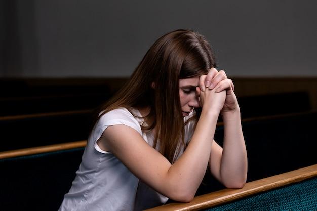 Een droevig christelijk meisje in wit shirt zit en bidt met nederig hart in de kerk
