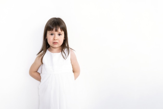 Een droevig en bang meisje bevindt zich op een witte achtergrond. een verward kind staat tegen de muur.
