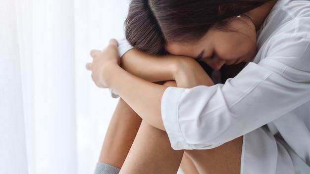 Een droevige en beklemtoonde jonge aziatische vrouw die alleen in slaapkamer zit
