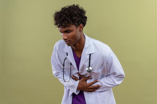Een droevige jonge knappe dokter met een donkere huid en krullend haar, gekleed in een witte jas met een stethoscoop die zich slecht voelt terwijl hij zijn buik aanraakt op een groene ruimte