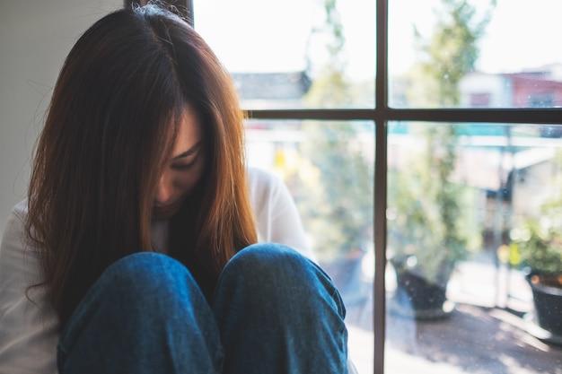 Een droevige jonge vrouw die alleen in de kamer zit