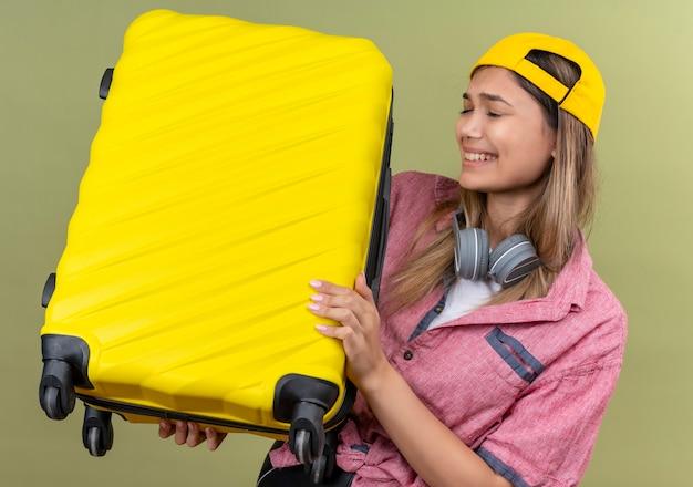 Een droevige jonge vrouw die rood overhemd en gele honkbalhoed met hoofdtelefoons draagt die gele koffer op een groene muur houden