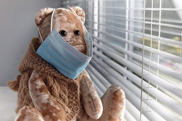 Een droevige teddybeer met een medisch masker kijkt uit het raam
