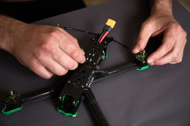 Een drone samenstellen uit onderdelen met behulp van gereedschap highspeed race-quadcopter voorbereiden op de vlucht