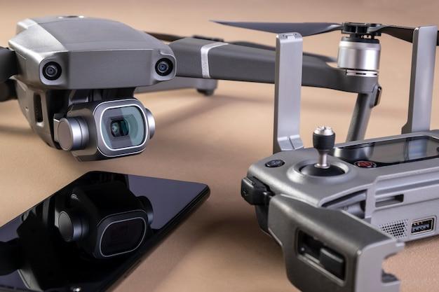 Een drone, zijn controller en een smartphone op een bruin oppervlak. Premium Foto