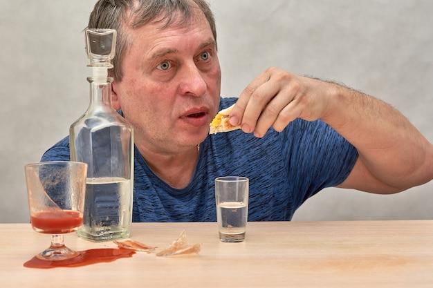 Een dronkaard die aan een tafel zit, grijpt alleen alcohol