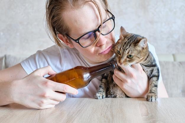 Een dronken man biedt zijn kat een drankje aan.